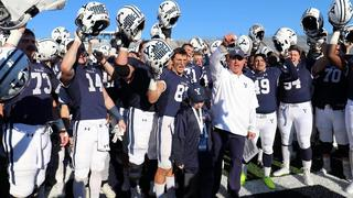Yale footbal team blue unifrom helmets raised smiling