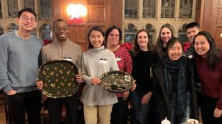 Students in Saybrook College pose with empty plates at the end of their study break.