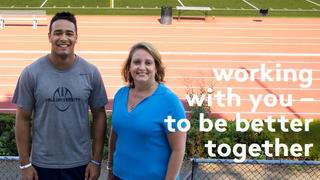 Two people standing infront of running track