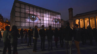 Crowd looking at giant light box on building of human eyes