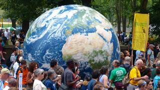 Crowd surrounding giant planet Earth installation