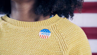 "Stock image of a woman with an ""I voted"" sticker on her sweater"