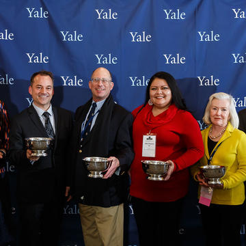 Alumni holding their AYA Leadership Award trophies.